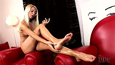 The camera captures every inch of her feet as she oils them up